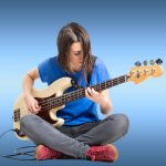 Teenage girl having bass guitar lessons with Christensen's
